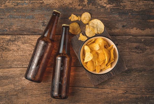 나무 배경에 있는 그릇에 어두운 맥주 병과 칩. 평면도. 옥토버페스트.
