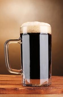 茶色の木製テーブルのマグカップにダークビール