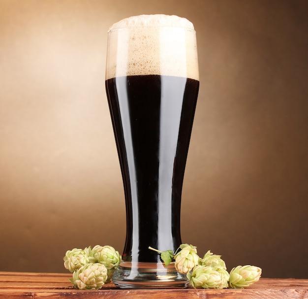 ガラスのダークビールと茶色の壁の木製テーブルの上の緑のホップ