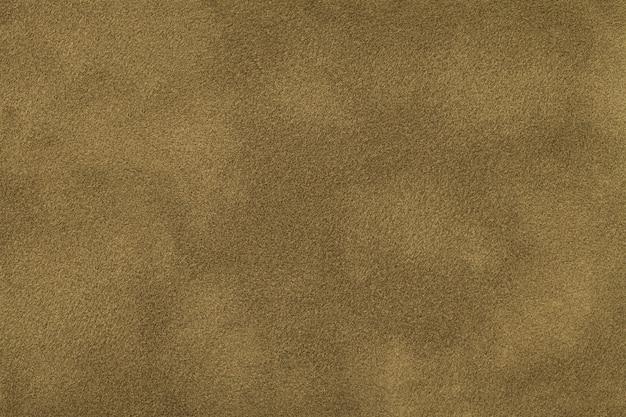 Dark beige matte background of suede fabric, closeup. velvet texture of seamless brown felt textile, macro.