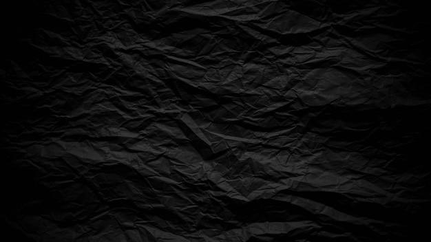 Dark black crumpled paper close up texture background