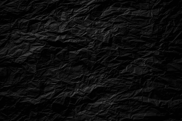 Dark black crumpled paper close up texture background