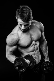 Dark black and white contrast shot of young muscular fitness man stomach arm. working out with dumbbells isolated