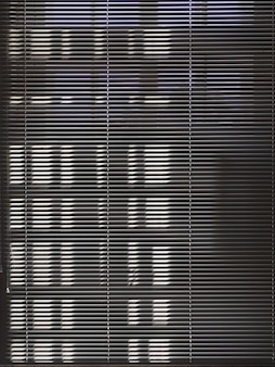 Темные шторы закрывают солнечное окно. темный фон окна