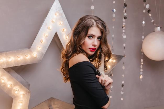 Dark blond girl with red lipstick in black elegant top posing against glowing star