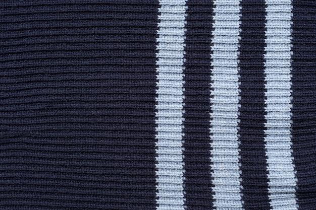 Темно-синие и белые полосы связаны спицами спицами.