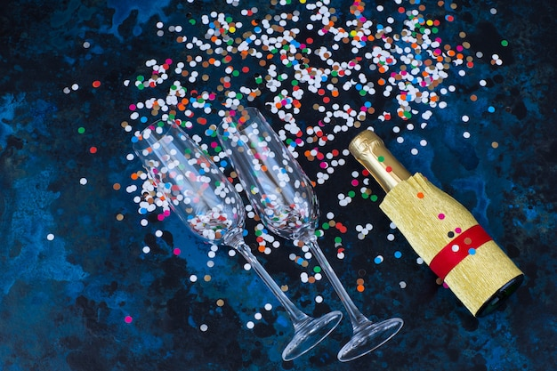 On dark blue background are two champagne glasses, a bottle of champagne and confetti
