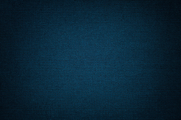 Dark blue background from a textile material. fabric with natural texture. backdrop.