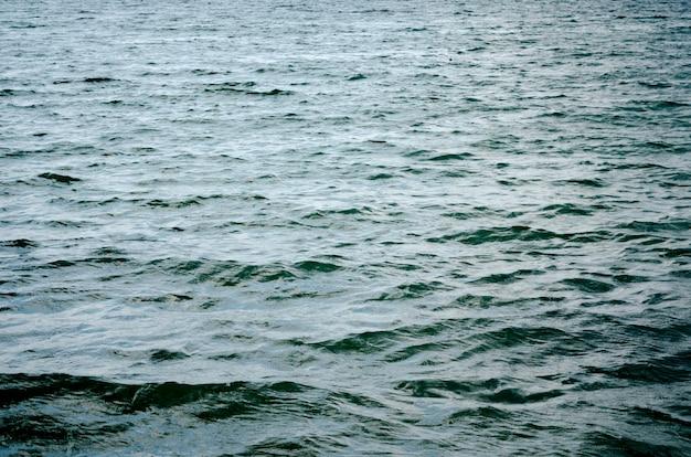 水面の暗い青色の背景。海の水面のテクスチャ。深海の波
