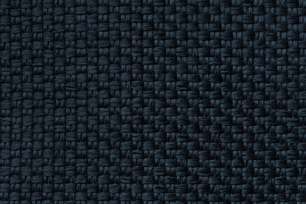 Dark blue background with checkered pattern, closeup. structure of the fabric macro.