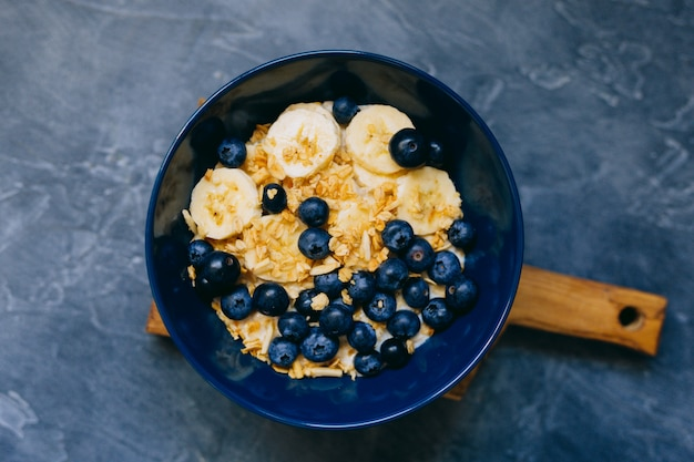 Dark blue bowl of oatmeal porridge with banana and blueberry on vintage table top view in flat lay style. hot breakfast and homemade food. free space. homemade cuisine.