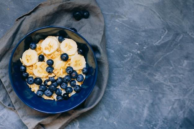 Синий шар овсяной каши с бананом и черникой на старинном настольном представлении в плоском стиле положения. горячий завтрак и домашняя еда. свободное место. домашняя кухня.
