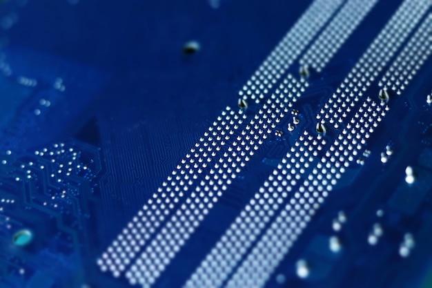 Dark blue computer motherboard closeup in tilt shift style selective focus defocused