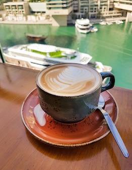 Темно-синяя чашка капучино на столе с видом на реку, яхты и лодки. утренний завтрак. выборочный фокус.