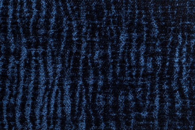 Dark blue fluffy background of soft, fleecy cloth, texture of textile closeup