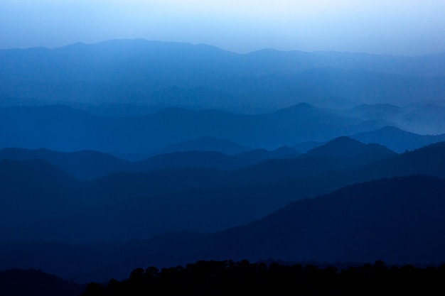 Dark blue mysterious mountain landscape in cloudy sunset sky
