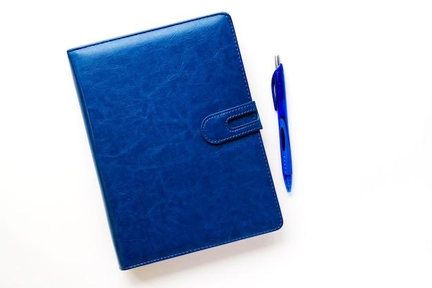 밝은 배경의 가죽 케이스에 짙은 파란색 노트북 손잡이가 옆에 있고 계획 중입니다.