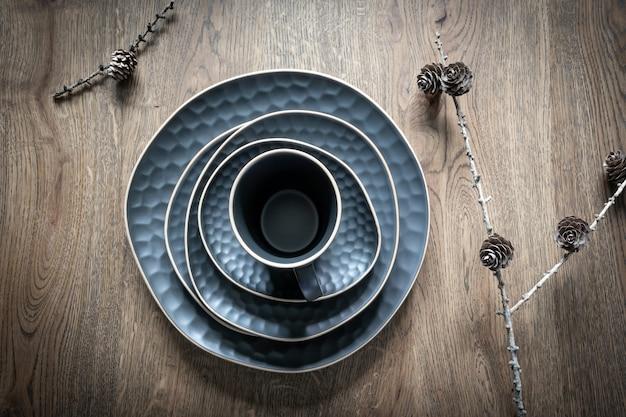 ダークブルーの料理セット:マグカップ、ソーサー、プレート、ボウル、木製の背景の小枝に乾いたカラマツの円錐形。クリスマスのテーブルデコレーション、魔法の休日