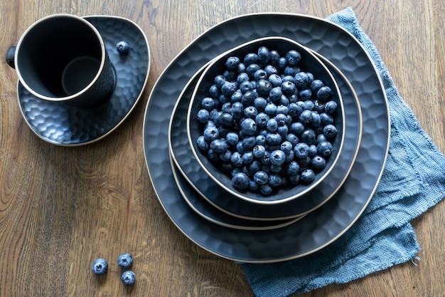 나무 배경에 진한 파란색 세트의 요리. 블루베리 한 접시. 마법의 베리, 여름 휴가. 평면도.