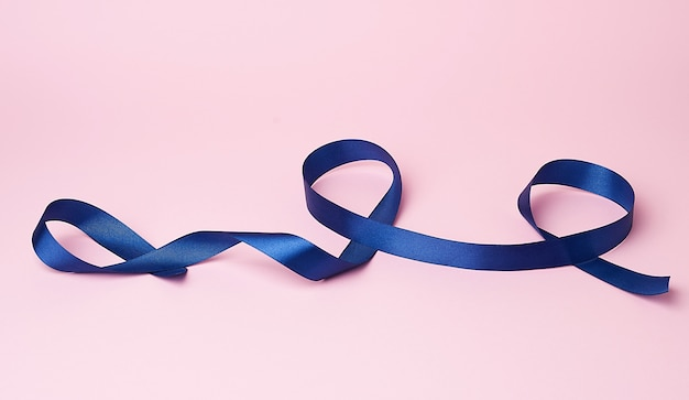 Dark blue silk ribbon twisted into loops on a pink surface