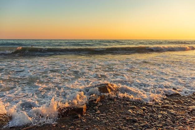 Темно-синие волны на фоне красивого оранжевого заката на черном море, анапа, россия