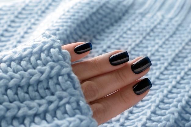 Темно-синий зимний маникюр гель-лак на ногтях крупным планом.
