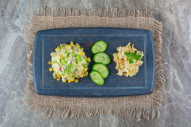 Bordo scuro di insalata di mais e piselli sulla superficie di marmo.