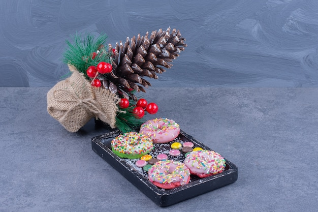 A dark board full of donuts with sweet jelly candies