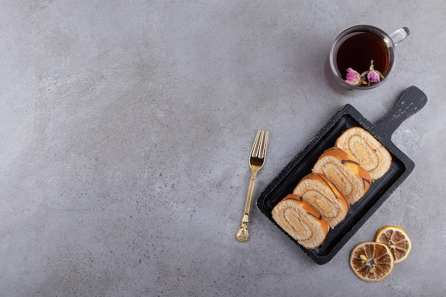 스위스 롤 케이크의 다크 보드와 돌에 뜨거운 차 한잔.