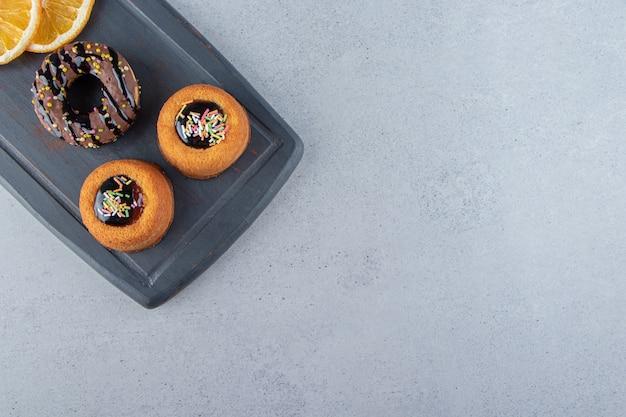 맛있는 초콜릿 도넛과 젤리 케이크의 다크 보드. 고품질 사진
