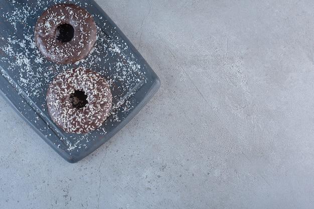 Tavola scura di gustose ciambelle al cioccolato su fondo di pietra.
