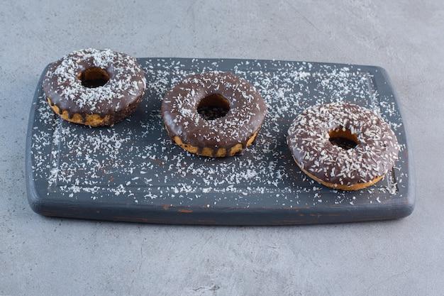 Dark board of tasty chocolate donuts on stone.