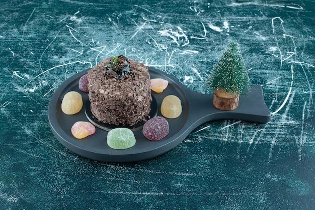 A dark board with chocolate cake with sweet marmalade. high quality photo