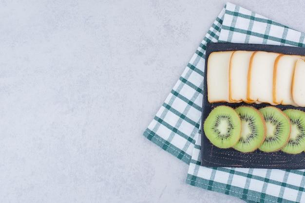 Un tagliere scuro con fette di pane e kiwi fresco. foto di alta qualità