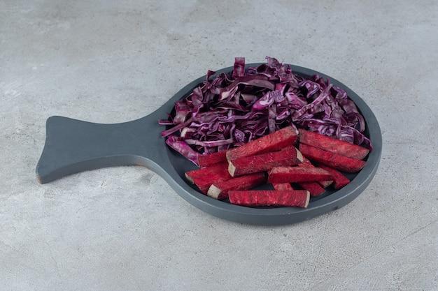 Un tagliere scuro con fettine di cavolo e barbabietola. foto di alta qualità