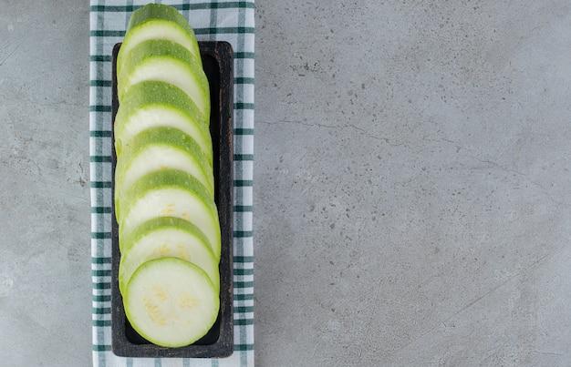 Una tavola scura con zucchine a fette su uno sfondo grigio. foto di alta qualità