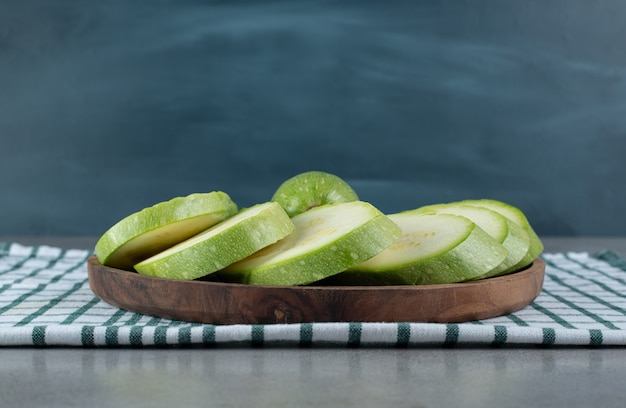 Un tagliere scuro con verdure di zucchine a fette. foto di alta qualità
