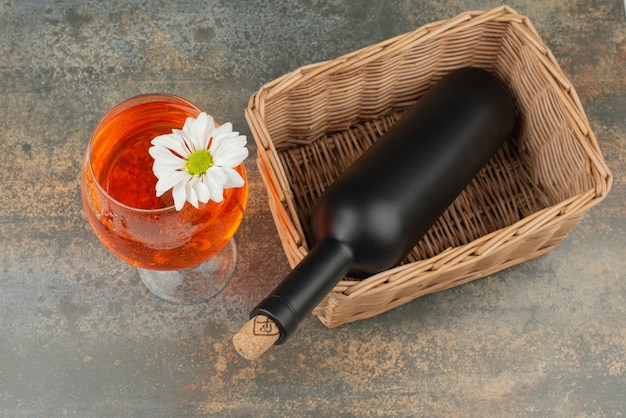 Dark bottle on basket with glass of juice on marble background. high quality photo