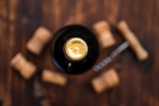 A dark bottle of wine next to blurry a corkscrew and corks on a wooden table