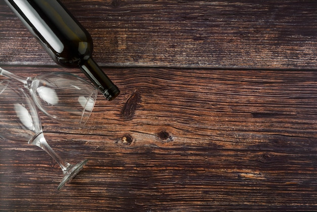 Dark bottle of wine and glasses on wooden background. top view with copy space.