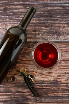 Dark bottle of wine and glasses on wooden table. top view with copy space.