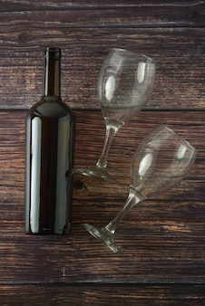 Dark bottle of wine and glasses on wooden table. top view.