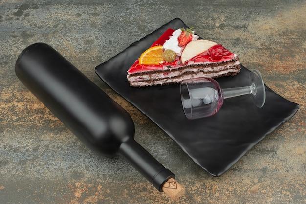Bottiglia scura con una gustosa fetta di torta sul piatto