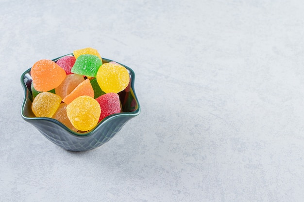 Dark bowl of colorful jelly marmalades on marble background.
