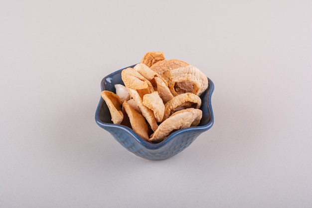 Dark bowl of dry apple rings placed on white table. high quality photo