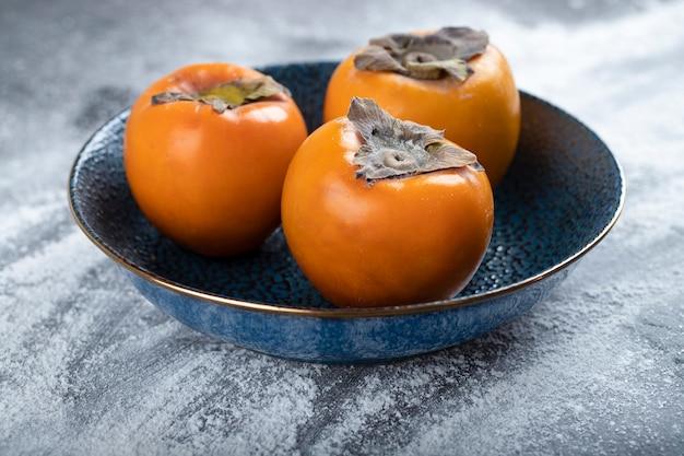Dark bowl of fresh persimmon fruits on dark surface.