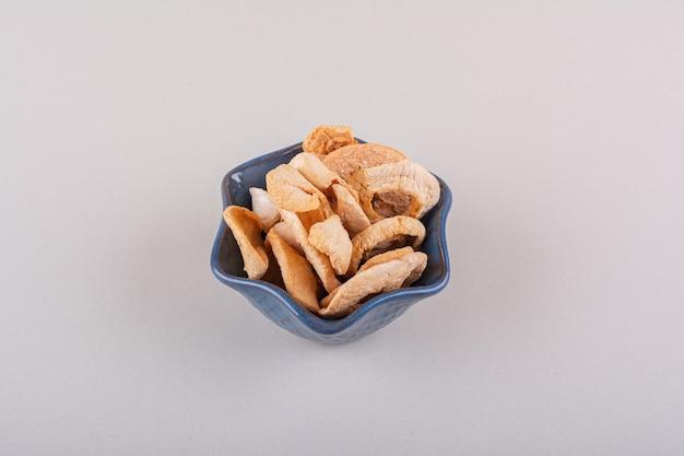 하얀 탁자 위에 놓인 마른 사과 반지의 어두운 그릇. 고품질 사진