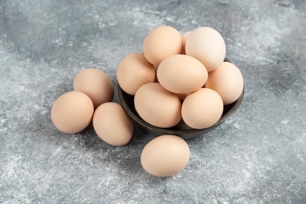 대리석에 신선한 생 쌀된 계란의 어두운 그릇.
