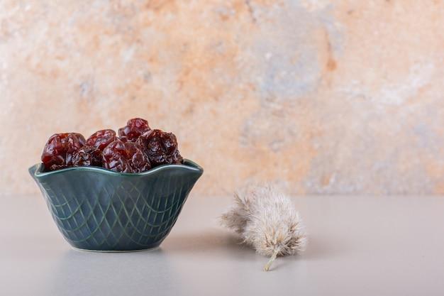 白いテーブルの上の有機乾燥ナツメヤシの暗いボウル。高品質の写真