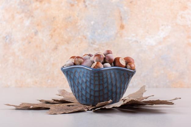 흰색 배경에 껍질을 벗긴 천연 헤이즐넛과 마른 잎의 어두운 그릇. 고품질 사진